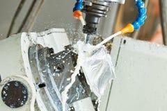 Malningmetallarbete Cnc-metall som bearbetar med maskin vid lodlinje, maler med kylmedlet arkivbild