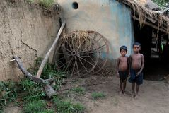 Malnourished Children in India. September 05, 2011.Bolepur,Birbhum,West Bengal,India,Asia-Two tribal boy standing in-front of their traditional house in the Stock Photography