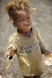 A Malnourished Haitian Girl Eating. Overhead view of a malnourished Haitian girl looking at her benefactors as she eats the peanutbutter bread given to her Royalty Free Stock Photography