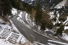 Maloja pass road hairpin turns  , Switzerland. Landscape with some cars on hairpin turns of Maloja pass road  in winter mountain landscape, shot in cloudy winter Stock Images