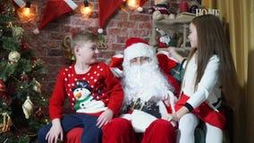 Malos muchacha y muchacho con el buen comportamiento de sentarse en el revestimiento de Santa Claus almacen de video