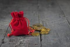 Malote vermelho de veludo com moedas em uma tabela de madeira do vintage imagens de stock royalty free