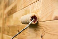Malować drewnianą ścianę z farba rolownikiem Zdjęcia Royalty Free