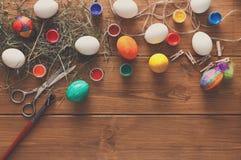 Malować kolorowego Easter jajek tło, odgórny widok na drewnie Obrazy Stock