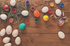 Malować kolorowego Easter jajek tło, odgórny widok na drewnie Zdjęcia Stock