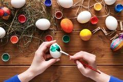 Malować kolorowego Easter jajek tło, odgórny widok na drewnie Zdjęcie Royalty Free