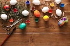 Malować kolorowego Easter jajek tło, odgórny widok na drewnie Zdjęcie Stock