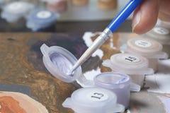 Malować na kanwie liczbami Kobieta trzyma rysunek i muśnięcie ja Liczący zbiorniki z farbami i muśnięciami na canva obrazy stock