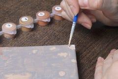 Malować na kanwie liczbami Kobieta trzyma rysunek i muśnięcie ja Liczący zbiorniki z farbami i muśnięciami na canva fotografia stock