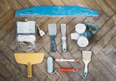 Malować narzędzia i akcesoria na drewnianej podłoga, kit knifes, farba rolownik, muśnięcia, respirator Fotografia Stock