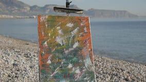 Malować obrazek na plaży W górę nowożytnego abstrakta ostatnio zrobił obraz pozycji na metal sztaludze na seashore zbiory wideo