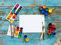 Malować set: muśnięcia, farby, kredki, akwarela, biały papier Fotografia Stock