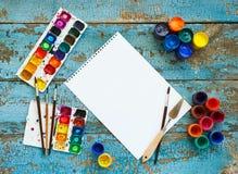 Malować set: muśnięcia, farby, kredki, akwarela, biały papier Obraz Royalty Free