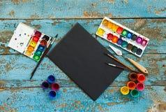 Malować set: muśnięcia, farby, kredki, akwarela, czerń papier Fotografia Stock