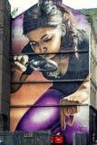 Malowidło ścienne pokazuje dziewczyny z powiększać - szkło Obrazy Stock