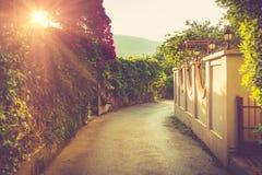 Malownicza wąska ulica dekorował z obfitością kwiaty przy światłem słonecznym Budva Montenegro Zdjęcia Royalty Free