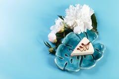 Malowniczy życie w błękicie wciąż tonuje, dekoracyjny talerz z kawałkiem otaczającym białymi pions cheesecake, błękitny tło, kopi Obraz Stock