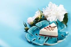 Malowniczy życie w błękicie wciąż tonuje, dekoracyjny talerz z kawałkiem otaczającym białymi pions cheesecake, błękitny tło, kopi Obraz Royalty Free