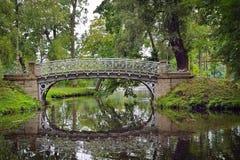 Malowniczy krajobraz z starym mostem nad przepływem w parku Obrazy Royalty Free
