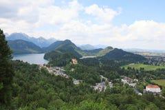 Malowniczy pogórza Alps jezioro otaczający z niskimi skałami przerastać z zwartym drewnem są widoczni stary ca zdjęcia stock