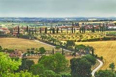 Malowniczy Tuscany krajobraz z tocznymi wzgórzami, doliny, pogodni pola, cyprysowi drzewa wzdłuż meandrować wiejską drogę, domy n zdjęcia stock
