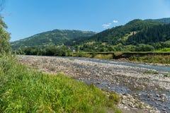 Malowniczy widok płytka halna rzeka przeciw tłu piękna wioska Obrazy Stock