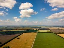 Malowniczy widok z lotu ptaka ziemia uprawna w wsi, niebieskie niebo z bielem chmurnieje, kolorowi pola z różnymi uprawianymi upr obrazy stock