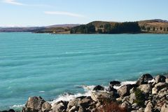 Malowniczy wybrzeże z spektakularny chabeta głęboką błękitną wodą, odległymi drzewami i górami, zdjęcie stock