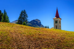 Maloya churchtower in summer. Picturesque church tower with a red roof of Maloja near St. Moritz above a meadow during summer under a clear blue sky. Engadin Royalty Free Stock Photos