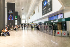 Milan-Malpensa airport arrivals hall with people on waitig. Ferno, Italy - July 11, 2016: Milan-Malpensa airport arrivals hall with people on waitig Royalty Free Stock Images