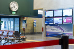 Malpensa airport interior. Milano Malpensa airport interior scene with chairs, info boards and clock on the wall in Milan, Italy Stock Images