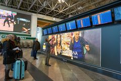 Malpensa Airport. MILAN MALPENSA, ITALY - CIRCA NOVEMBER, 2017: passengers standing in front of the flight information display monitors at Milan-Malpensa airport Royalty Free Stock Image