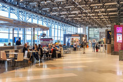 Malpensa airport Terminal 2 interior view. MILAN, ITALY - SEPTEMBER 22, 2015: People sitting in cafe and walking inside Terminal 2 currently used by EasyJet in Stock Images