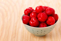 Malpighia glabra red acerola, tropical fruit. In bowl on gray background. Selective focus Royalty Free Stock Image