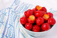 Malpighia glabra (red acerola), tropical fruit in bowl. On white background. Selective focus Stock Images