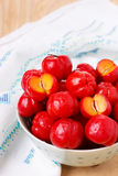 Malpighia glabra (red acerola), tropical fruit. Tropical fruit Malpighia glabra (red acerola) in bowl on wooden table. Selective focus Stock Images