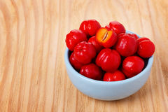 Malpighia glabra (red acerola), tropical fruit. In bowl on wooden table. Selective focus Royalty Free Stock Photography