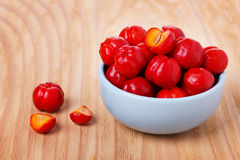 Malpighia glabra red acerola, tropical fruit in bowl. On wooden table. Selective focus Stock Photos