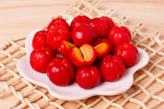 Malpighia glabra red acerola, tropical fruit i. N bowl on wooden table. Selective focus Royalty Free Stock Photography