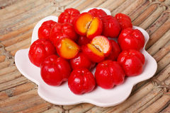 Malpighia glabra (red acerola), tropical fruit. Tropical fruit Malpighia glabra (red acerola) on plate on wooden table. Selective focus Stock Image