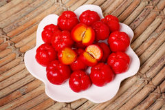 Malpighia glabra (red acerola), tropical fruit. On plate on wooden table. Selective focus Stock Images