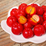 Malpighia glabra red acerola, tropical fruit. Tropical fruit Malpighia glabra red acerola on plate on wooden table. Selective focus Royalty Free Stock Photos