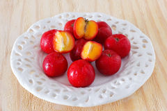Malpighia glabra (red acerola), tropical fruit. On white plate. Selective focus Royalty Free Stock Images