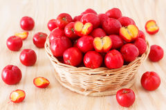 Malpighia glabra (red acerola), tropical fruit in wicker busket. On wooden table. Selective focus Royalty Free Stock Images