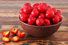 Malpighia glabra (red acerola), tropical fruit on wooden table. Selective focus Royalty Free Stock Images