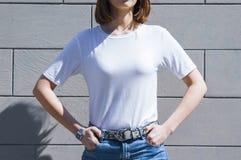 Malplaatje en stellen van het van de model het lege witte t-shirt en denim tegen grijze straatmuur, voor drukopslag vector illustratie
