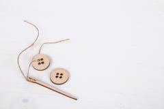 Malplaatje met houten naald en knopen Stock Fotografie