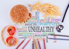 Malsano la inscripción en la tabla Concepto de la dieta sana, de la forma de vida, del cuerpo y de la salud mental foto de archivo libre de regalías