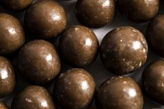 Malt Balls. With chocolate shot close up on a white background Stock Images
