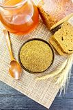Malt in bowl on board top. Malt in a bowl, spoon, bread, kvass in a jar on a wicker brown napkin on the background of wooden board from above Royalty Free Stock Image